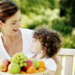 Healthy woman and son sitting outside in front of bowl of fruit