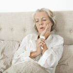 woman in bed with hand on cheek due to tooth infection