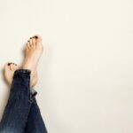 denim jeans with crossed bare feet with red nail polish